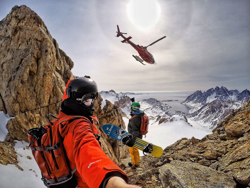 Rob and Seth throw up some stoke to the heli as they prepare to ride yet another perfect corn snow couloir down to the Arctic Ocean. Photo: Rob Kingwill