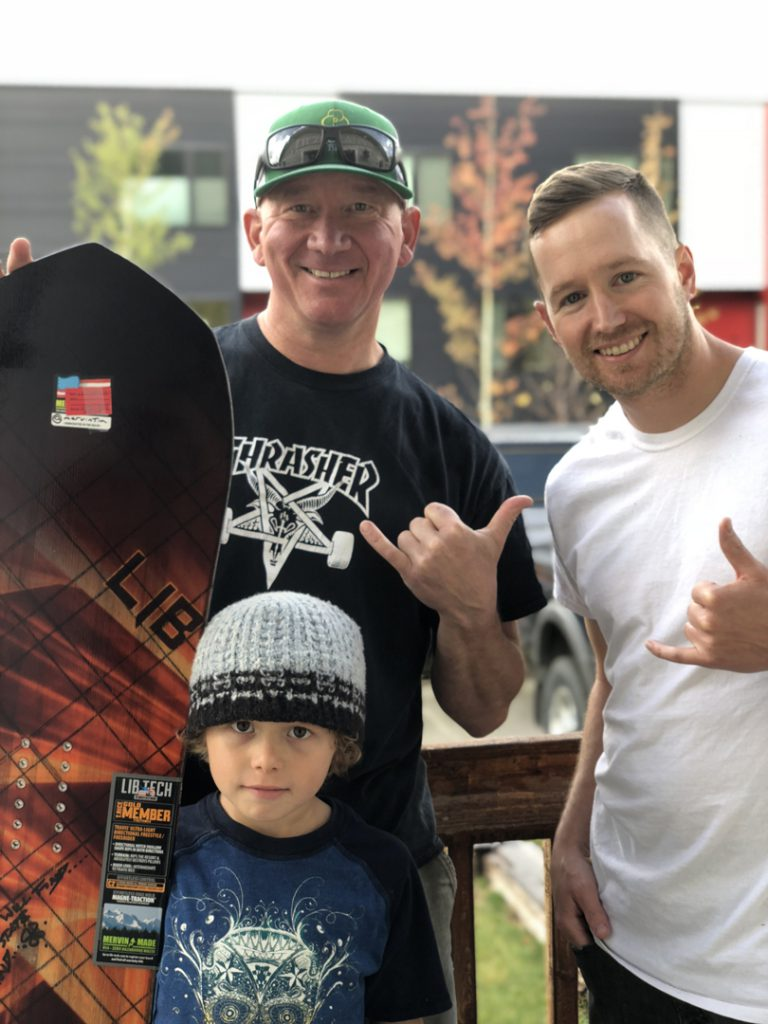 snowboarding. 18-19 JHSM. Adam Dowell with snowboard winner Jeff Musselman and Ryder. Jackson, Wyoming.