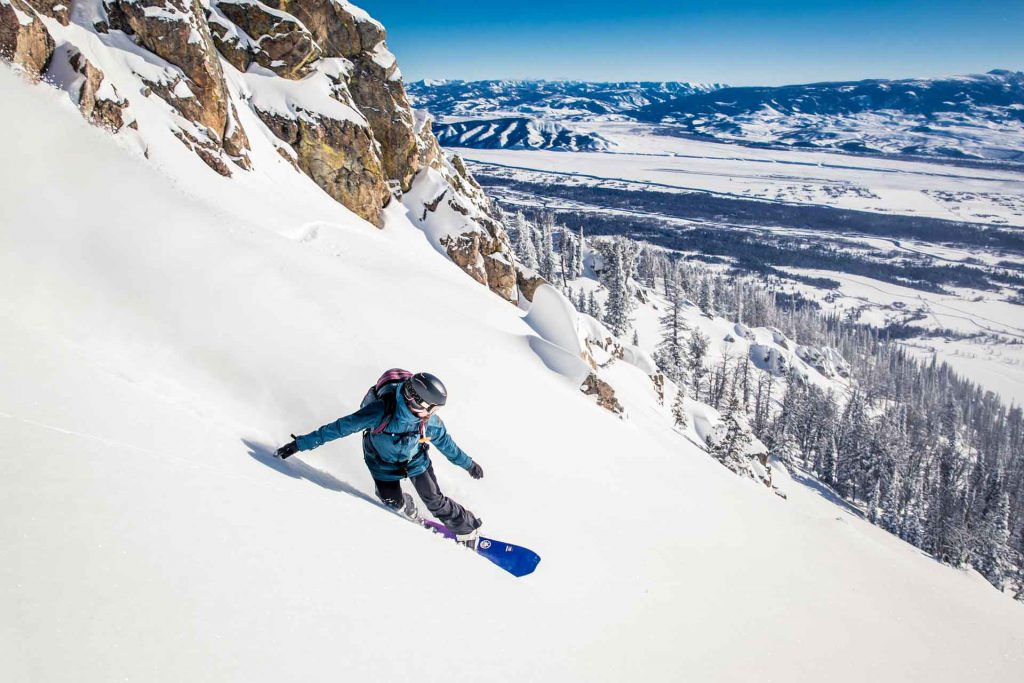 Snowboarder ripping through powder.
