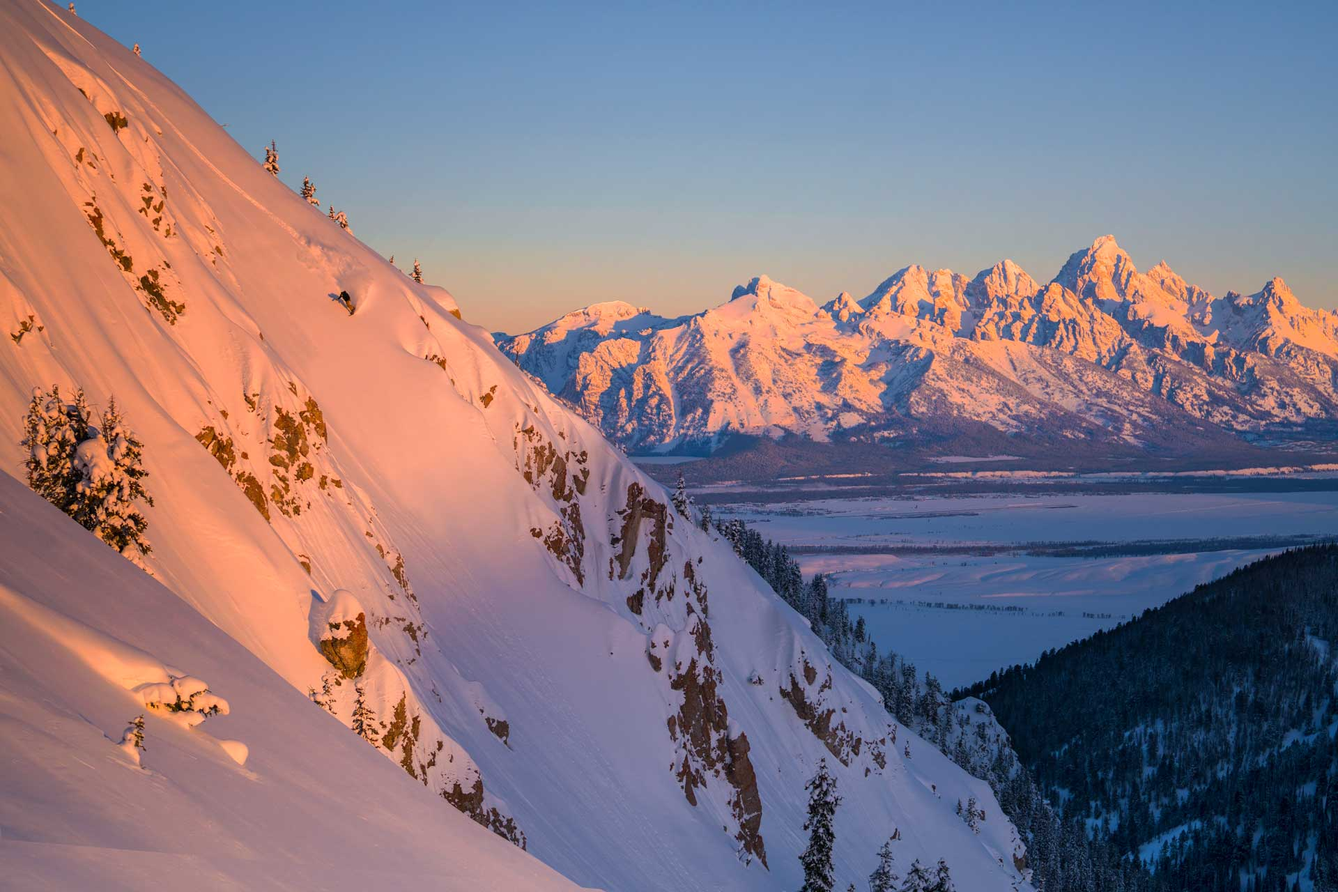 Snowboarder riding down mountain with the Grand Teton mountain range in the background.