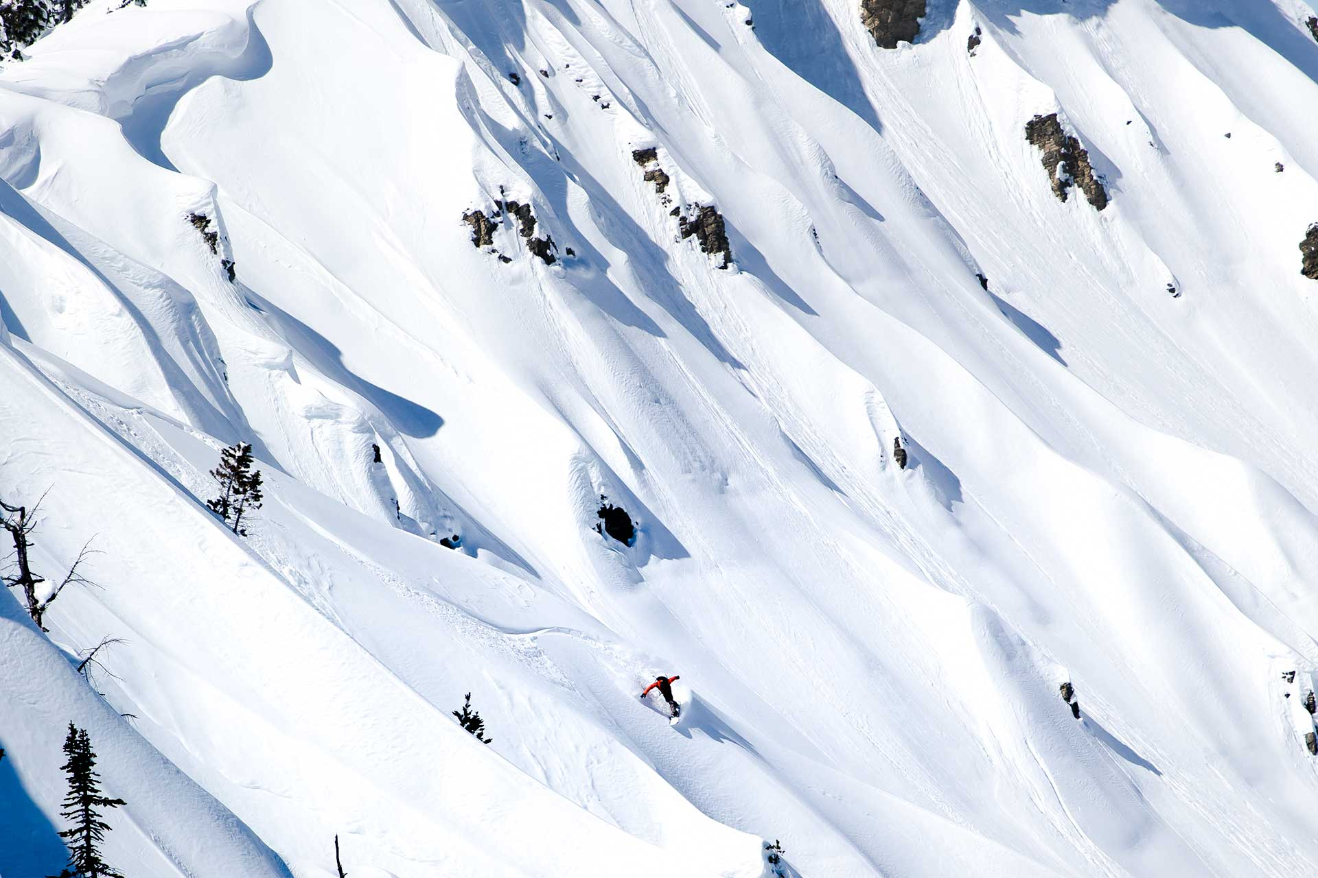 Snowboarder riding down through powder.