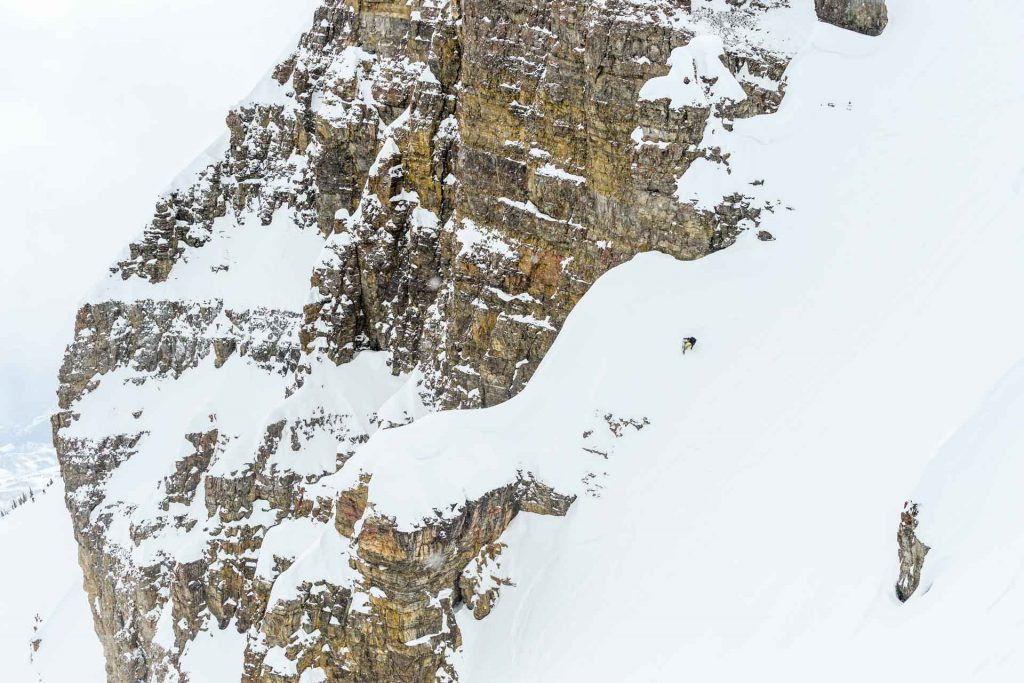 Snowboarder riding next to a huge cliff.