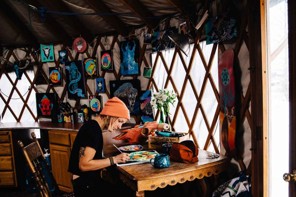 Artist Marinna Elinski working on a new illustration in her yurt.